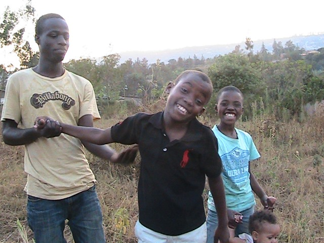 """I am happy because you helped us much to get money for land. We've been talking about getting land and praying for it for so long I didn't think it would happen, it is like a dream come true."" Ishimwe (10 years old) during his first visit to the plot pictured above with Armini, Joel and Keza"